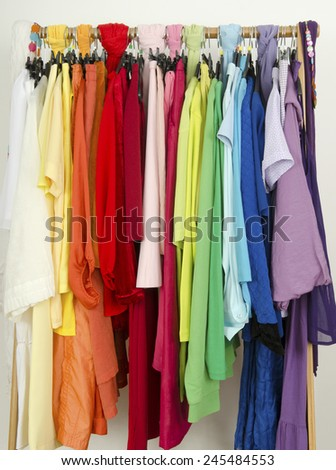 Close up on color coordinated clothes on hangers in a store. All colors clothes hanging on a rack nicely arranged. - stock photo