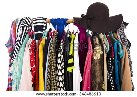 Close up on colorful clothes and hat on hangers in a store. Clothes and accessories hanging on a rack nicely arranged. - stock photo