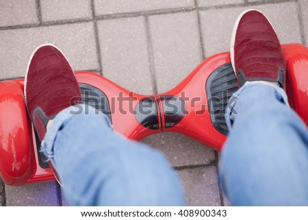 Close up on feet of a girl in marsala shoes riding on a modern red electric mini segway or hover board scooter.Trending new transportation technology that is fun and produces no air pollution at all - stock photo