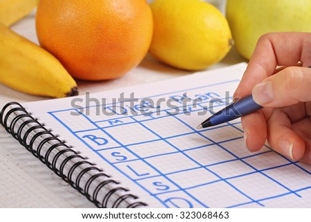 Close up on female hand writing diet plan. Nutritionist Doctor writing diet plan. Fit woman, Diet food, detox program, writing weight loss, healthy life style concept - stock photo