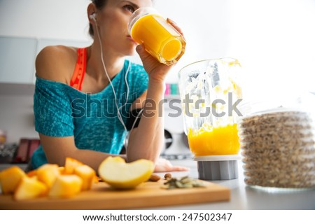 Close-up on fitness young woman drinking pumpkin smoothie in kitchen - stock photo