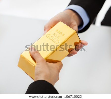 Close-up on hand of business people exchanging golden bar - stock photo