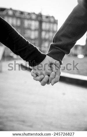 close up on hands of man and woman holding hands - stock photo