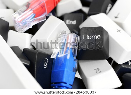 Close-up on on Black and White Computer Keyboard Keys in a pile with Red and Blue network cables. - stock photo