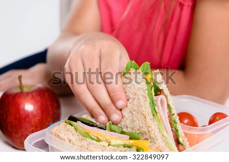 Close up on pair of young girl's hands removing a healthy wholesome wholemeal bread ham sandwich from her lunch box during lunch break - stock photo