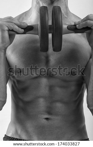 Close up on perfect abs. Strong bodybuilder with six pack and holding an abs roller - stock photo