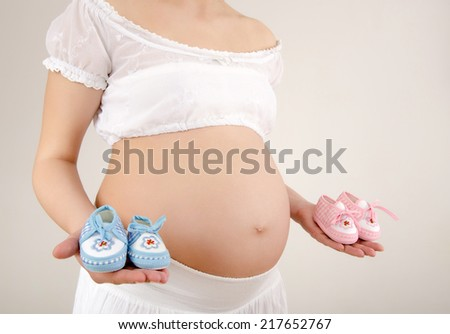Close up on pregnant belly with pink and blue new born shoes.. Woman expecting a baby dressed in white holding girl and boy baby boots. - stock photo