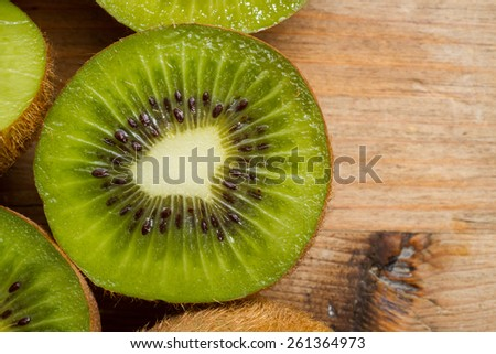 Close up on ripe half kiwi fruits against a rustic wooden background. Healthy eating. - stock photo