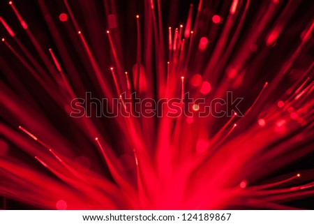 Close up on the ends of many illuminated fiber optic strands with black and blue blur background - stock photo