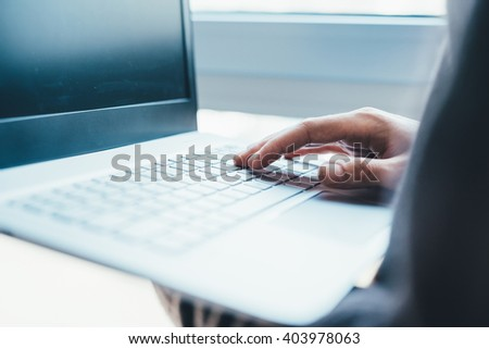 Close up on the hand on a businessman typing on the keyboard of a modern notebook hand hold - technology, business, working concept - stock photo