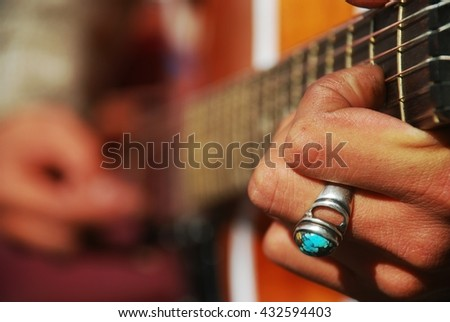 Close up on the hands of a guitarist - stock photo