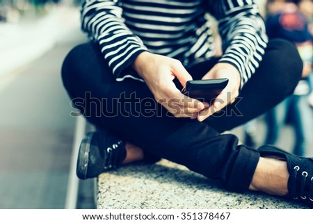 Close up on the hands of young handsome caucasian woman holding a smartphone, leg crossed, tapping the screen - technology, social network, communication concept - stock photo