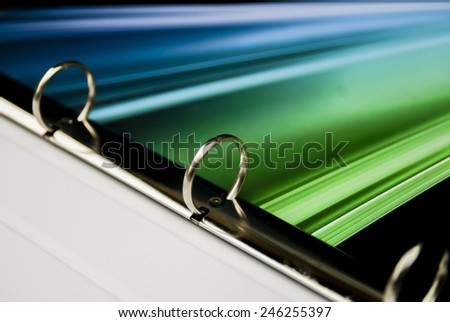 close up on the metallic curtains ring of colouristic brochure - stock photo