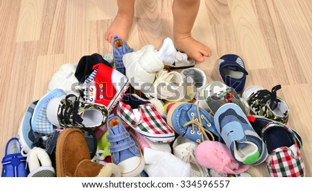 Close up on toddler legs near a lot of baby shoes. Untidy stack of child shoes thrown on the ground and baby feet.  - stock photo