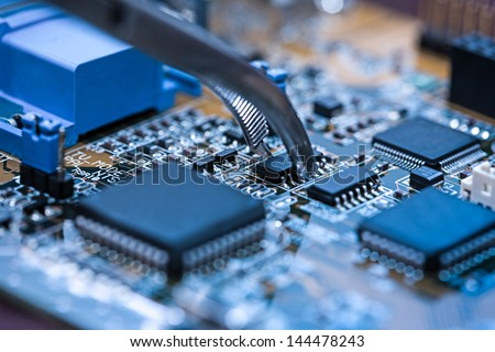 Close up on tweezers holding chip on computer circuit board. - stock photo
