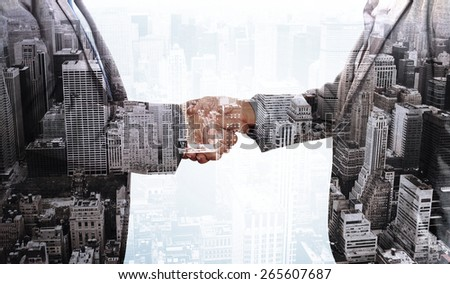 Close up on two businesspeople shaking hands against high angle view of city - stock photo