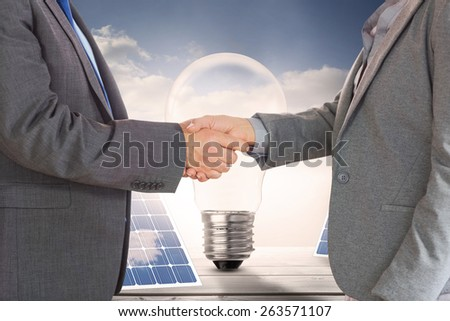 Close up on two businesspeople shaking hands against light bulb and solar panels on floorboards in the sky - stock photo