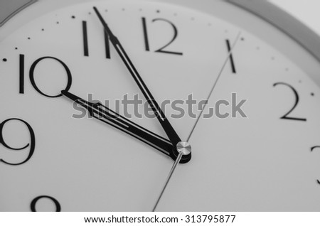 Close up on wall clock, office clock selective focus at needles  center in black and white. - stock photo