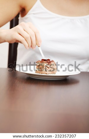 Close up on woman eating piece of cake. - stock photo