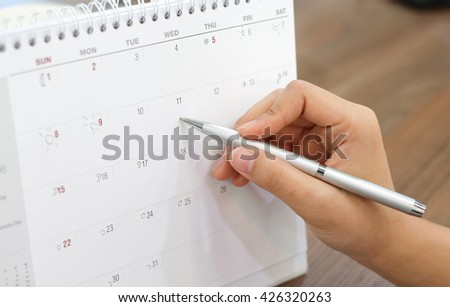 close up on woman hand with pen writing on calendar for note or make appointment:young girl try to drawing round the day in calendar about her vacation:traveling journey concept:holidays weekend - stock photo