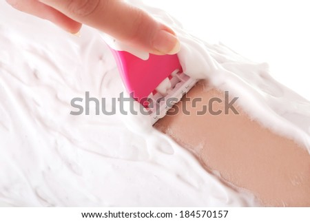 Close up on woman shaving her legs.  Over white. - stock photo