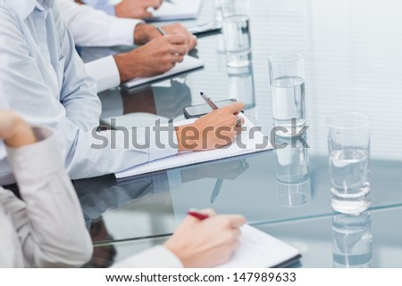 Close up on workmates hands taking notes during presentation in bright office - stock photo