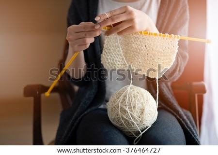 Close up on young woman's hands knitting. Sitting on old armchair near window - stock photo