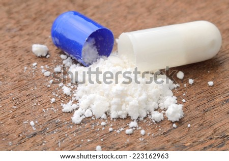 close up opened medicine capsule pill with powder on wood background - stock photo