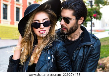 Close up outdoor fashion portrait of stylish young pretty couple in love hugs on the street of old town, wearing stylish total black leather rock n roll clothes ,sunglasses and hat. - stock photo