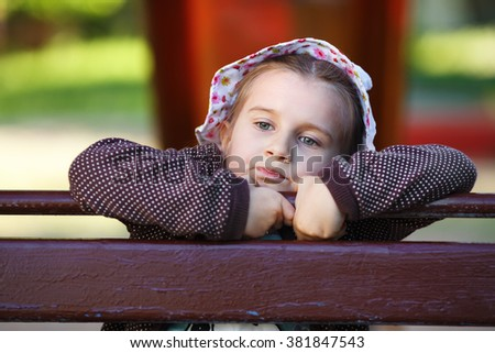 Close-up outdoor portrait of a serious little girl. Pensive child. Shallow depth of field. Selective focus. - stock photo