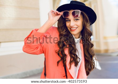 Close up  outdoor portrait of fashionable pretty woman   in casual bright spring or summer outfit , looking at camera, laughing.  Brunette  curly hairstyle. Bright sunny colors.  - stock photo
