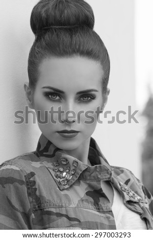 close-up outdoor portrait of pretty brunette girl with urban style and strong rock make-up. Wearing military shirt and creative hair-style , in black and white - stock photo