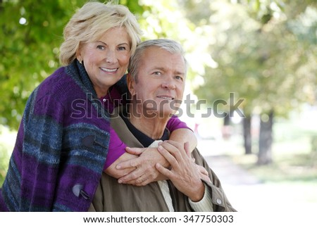 Close-up outdoor portrait of senior couple smiling to the camera while elderly woman hugging old man.  - stock photo