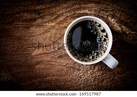 Close up overhead view of a cup of strong frothy espresso coffee on a rough textured wooden surface with dark vignetting and a highlight around the mug, with copyspace - stock photo