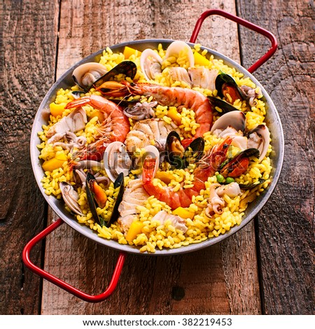 Close Up Overview of Colorful Spanish Seafood Paella Dish with Langostina and Shellfish Served in Shallow Pan with Red Handles on Rustic Wooden Table - stock photo