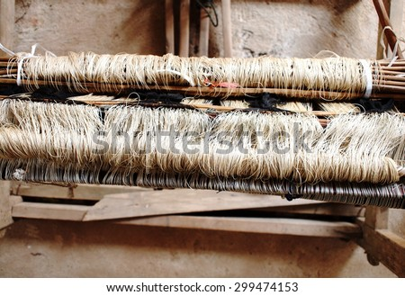 close-up parts of a manual small weaving machine and accessories for making traditional arts and crafts folklore textiles with natural hand made silk and cotton yarns in cultural village in THAILAND - stock photo