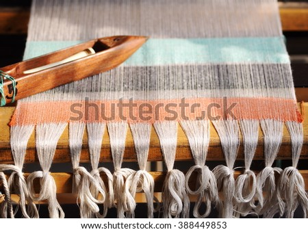 close-up parts of a manual small weaving machine for making education arts and crafts textiles with local traditional materials and yarns in a university's fashion and textiles workshop in THAILAND - stock photo