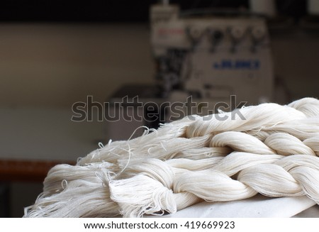 close-up parts of natural white cotton yarns for making traditional crafts folklore textiles with natural hand made silk and cotton in cultural design school workshop in THAILAND - stock photo