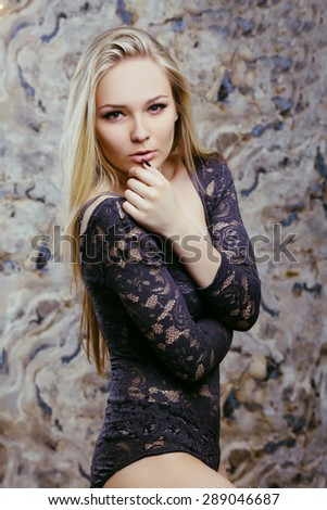 Close up passionate portrait of beautiful blonde young girl with long straight hair and perfect sexy body. In lacy swimsuit. - stock photo