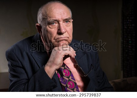 Close up Pensive Bald Senior Businessman Looking Into Distance While Resting his Chin on his Hand with Eyeglasses - stock photo