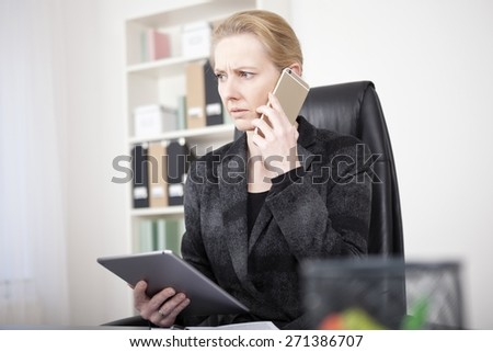 Close up Pensive Manageress in Black Business Attire Holding a Tablet Device While Calling to Someone Using Mobile Phone and Looking to the Left. - stock photo