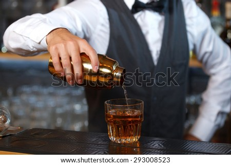 Close up photo of a bartender holding a golden shaker in his hand and pouring a cocktail in a low wide glass, shelves full of bottles with alcohol on the background - stock photo