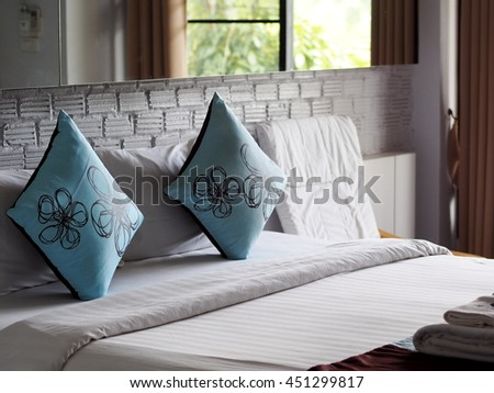 close up photo of a bed with blue brown color pillows in white painted bricks wall bed room boutique resort hotel under natural light from glass windows and reflecting on room mirror - stock photo