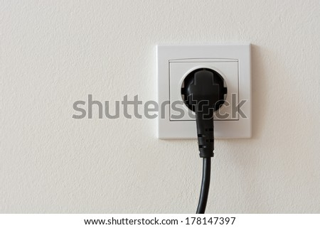 Close up photo of a black 220 volt power plug plugged in a socket with copyspace - stock photo
