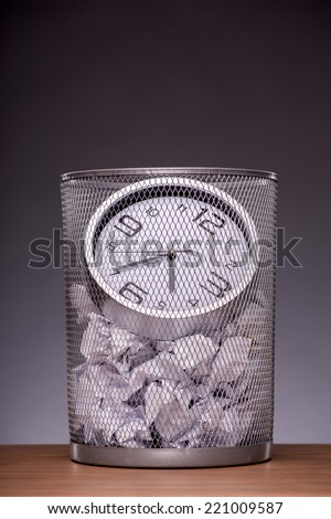 Close-up photo of a clock in refuse bin with other office rubbish standing on the table in office isolated on grey background with copy place, concept of time management at work - stock photo