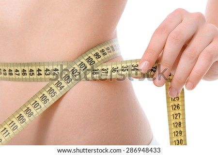Close up photo of a fit girl wearing white bra and panties ,holding a measuring tape with her hands on waistline, isolated on a white background - stock photo