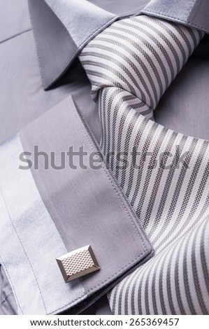 Close up photo of a folded grey shirt with a striped tie - stock photo