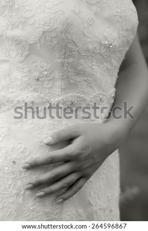 Close up photo of a hand of a woman wearing a wedding dress. Black and white photography - stock photo
