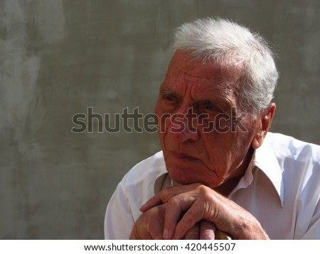 Close up photo of a retired old man in his eighties, leaning on his cane and thinking about the future and the past. - stock photo