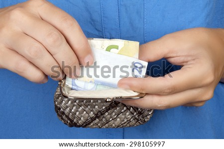 close up photo of a woman taking money out of her purse. - stock photo